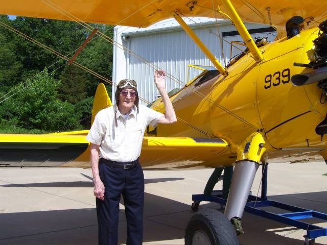 A Veteran poses with the Stearman Bi-Plane after taking a flight
