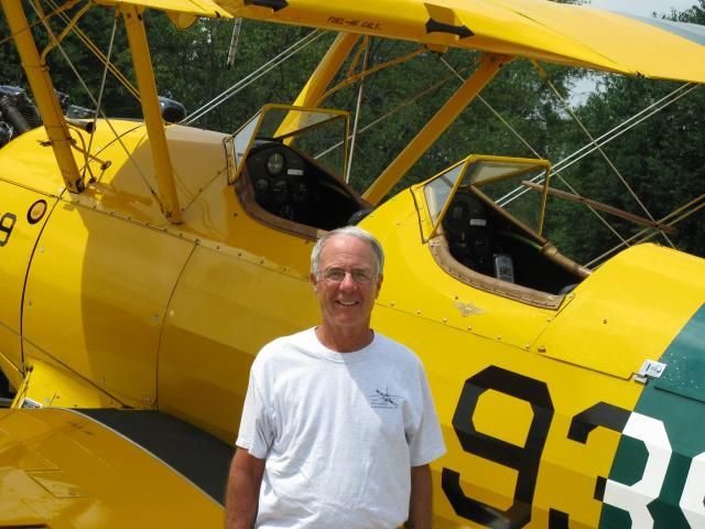 Former Naval Aviator and Air Zoo Board Member Alan Wright poses in front of his Stearman Bi-Plane